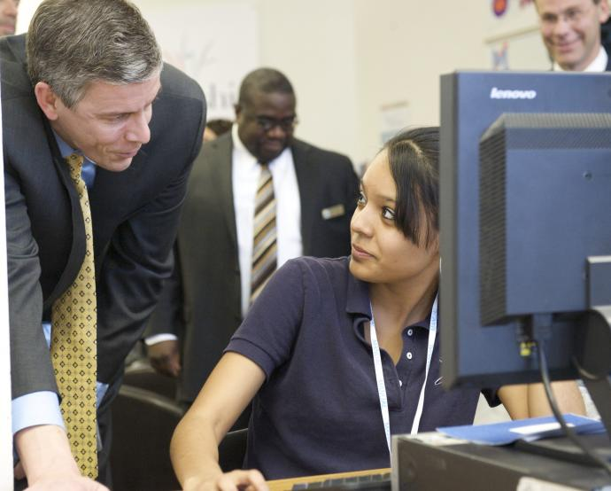 Secretary Arne Duncan watches a student in Denver, Colorado complete her FAFSA form online.